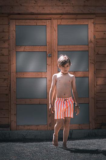 Full length portrait of boy standing against door