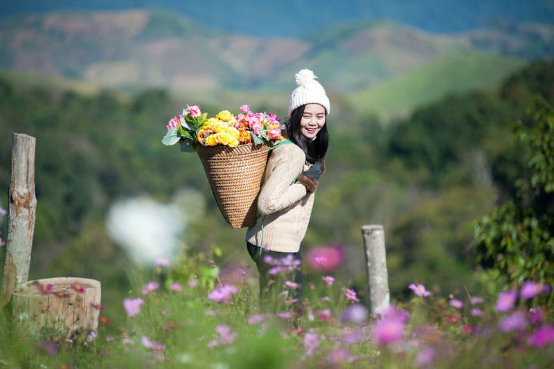 Smiling woman carrying flowers in basket