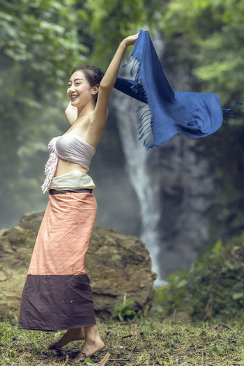 Woman wrapped in fabric on rock