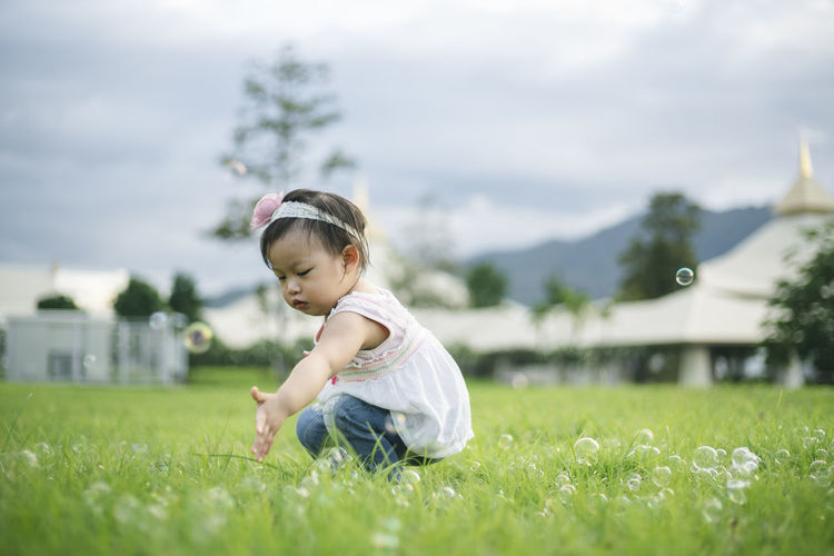 Side view of cute baby girl crouching on grassy land