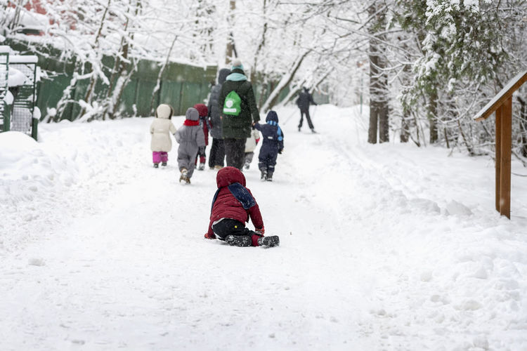 Group of unrecognizable litle kids with teachers of kindergarten, back to us, walk holding hands in snowy park, winter leisure, active lifestyles. Natural background, copy space Extreme Weather Snowing Outdoors Tobogganing Family Tree Snow Winter Cold Temperature Nature Sled White Color Child Day Childhood Warm Clothing Leisure Activity Leisure Winter Active Active Lifestyle  Kids Little Walking
