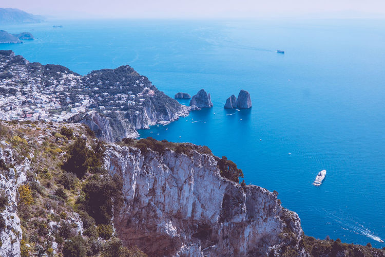 The scenic view of Capri from Monte Solaro, Sea Water Beauty In Nature Rock Tranquil Scene Scenics - Nature Horizon Over Water Tranquility Nature Rock - Object Horizon High Angle View Blue Sky Rock Formation Land Day Transportation Solid No People Outdoors Sailboat Capri Italy Blue Water Cliffs Seaside Ocean Paradise On Earth