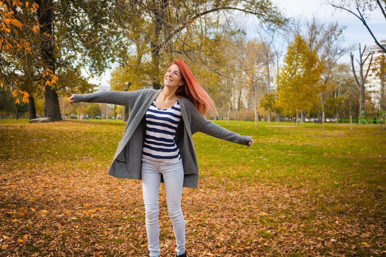 Autumn Young Adult Full Length One Person Adult Park Leaf Park - Man Made Space Happiness Change Women Nature Smiling Leisure Activity Outdoors Day Spinning Twirling Turning Arms Outstretched Happiness Carefree Freedom Redhead Autumn Enjoyment Copy Space Simple Life People One Woman Only Caucasian