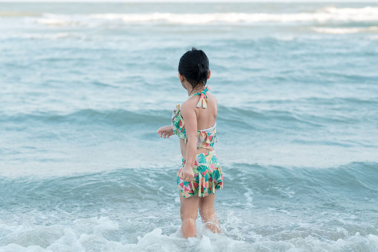 Rear view of child girl standing on beach