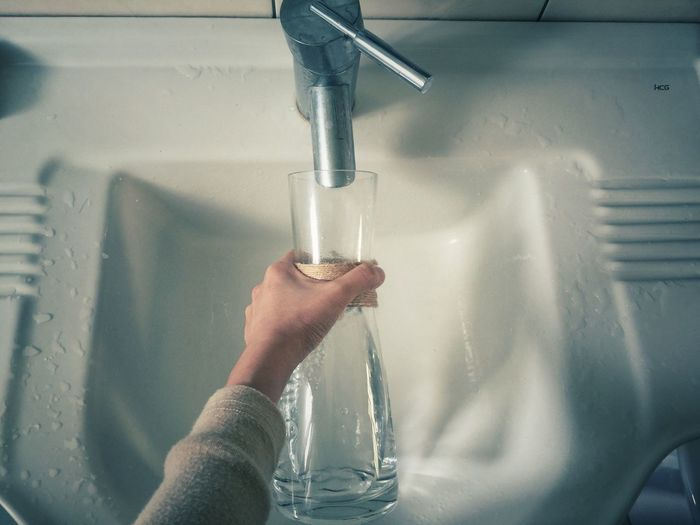 Cropped Hand Feeling Bottle In Sink
