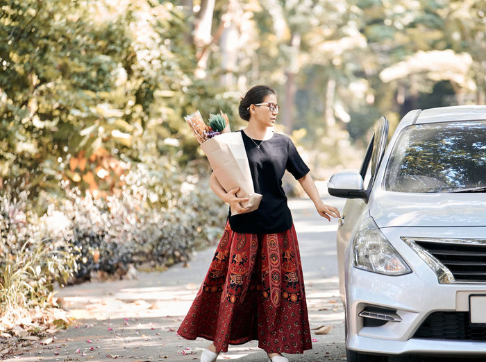 Full length of woman standing by car