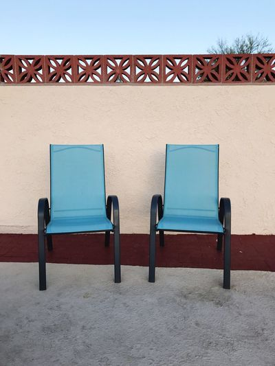 Two chairs in a pool recreation area AArchitecture dDay nNo People oOutdoors CClear Sky bBuilding Exterior sSky CChair cChairs cChairs Seats pPool Area pPool Chairs tTurquoise sSeats sSummer SSummertime