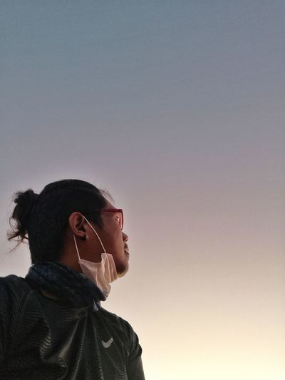 Low angle view of man looking at sky during sunset