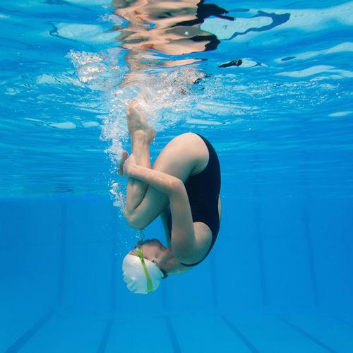 Woman wearing goggles swimming in pool
