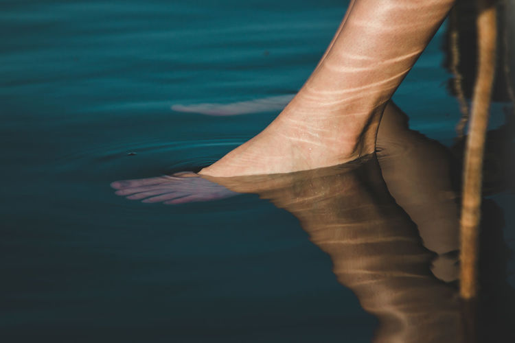 Low Section Of Woman Feet In Water At Lake