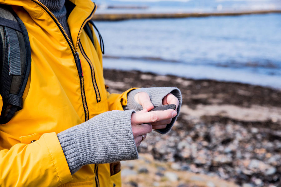 Beach Casual Clothing Clothing Day Focus On Foreground Hand Holding Human Hand Land Lifestyles Midsection Nature One Person Outdoors Real People Sea Standing Water Yellow