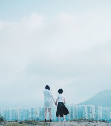 Rear view of women holding hands standing on hill