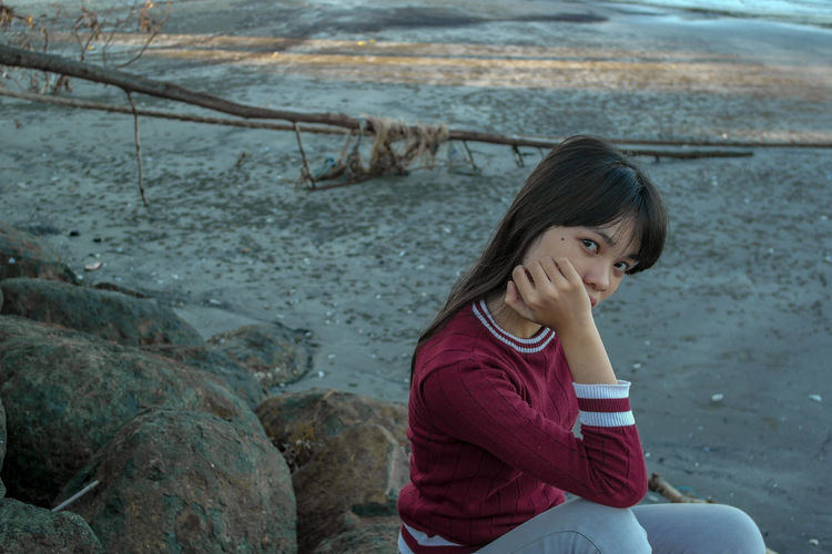 Portrait of girl sitting on rock by river
