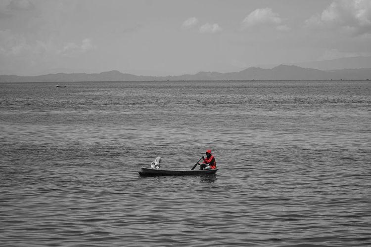 Men on boat in sea against sky