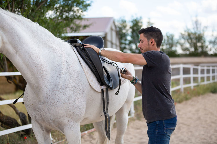Midsection of man riding horse in ranch