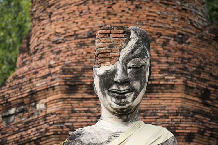Low angle view of old damaged buddha statue and temple