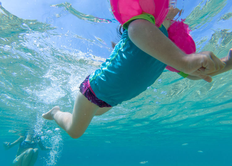 Low Section Of Girl Swimming In Sea