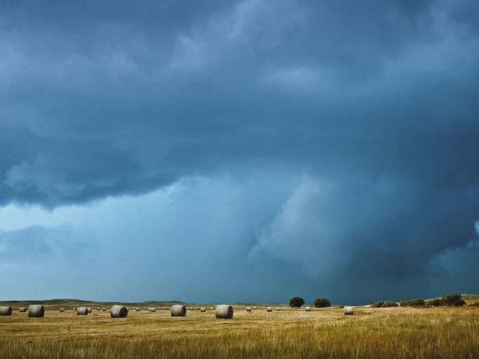 Hay Bales On Field Against Cloudy Sky