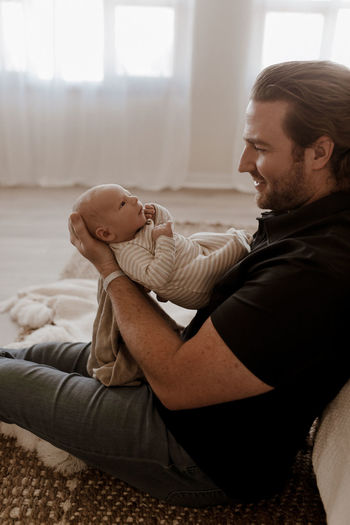 Side view of man holding baby at home
