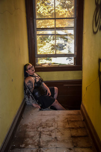 Young woman sitting on window in room