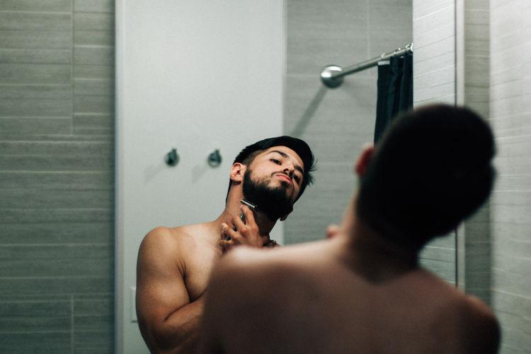 Full length of shirtless man standing in bathroom
