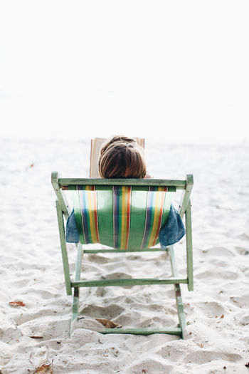 Rear view of woman with book lying on lounge chair at beach