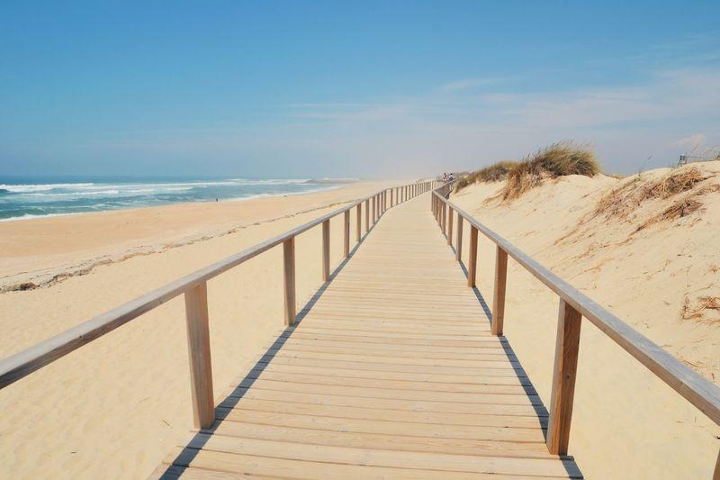 Empty boardwalk at beach against sky