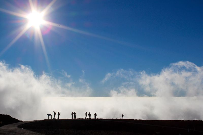 Silhouette People Against Bright Sun At Haleakala National Park