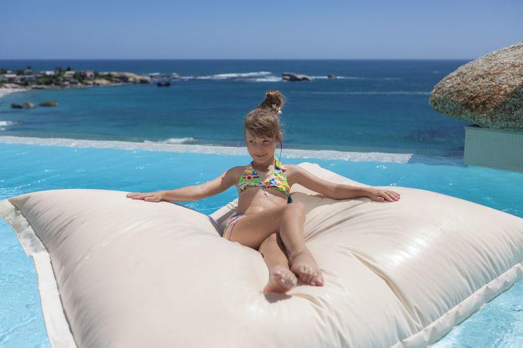 Girl wearing bikini lying on pool raft in infinity pool against clear blue sky