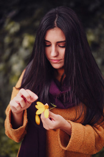 Beautiful young woman holding red flower
