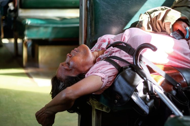 Midsection of woman lying on bench