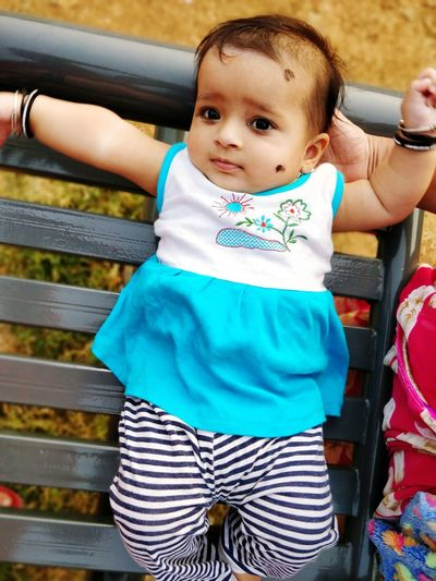 Portrait Of Cute Baby Girl Lying On Bench In Park