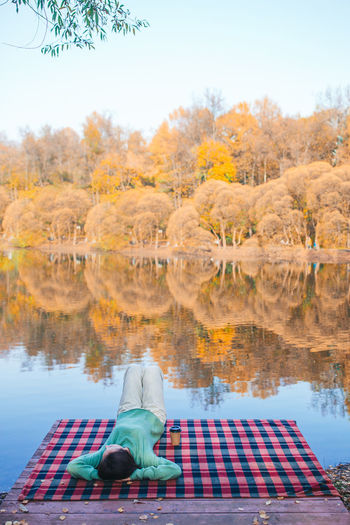 Rear view of man sitting by lake against sky during autumn