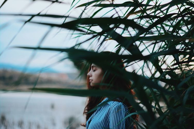 Young woman with eyes closed standing by plants