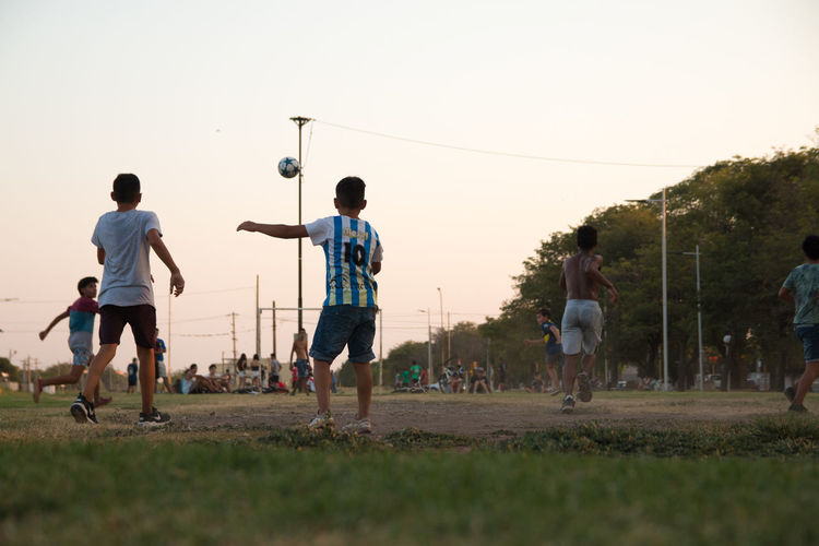 Group of people playing soccer on field against sky