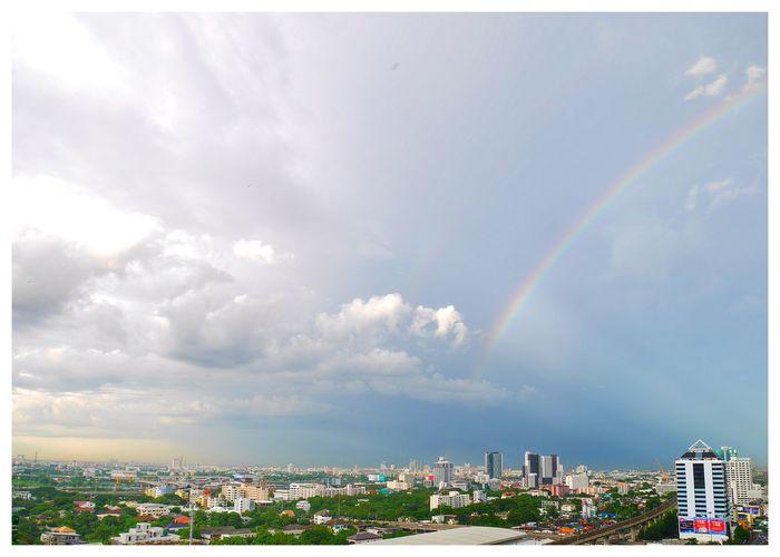 Rainbow over cityscape against sky