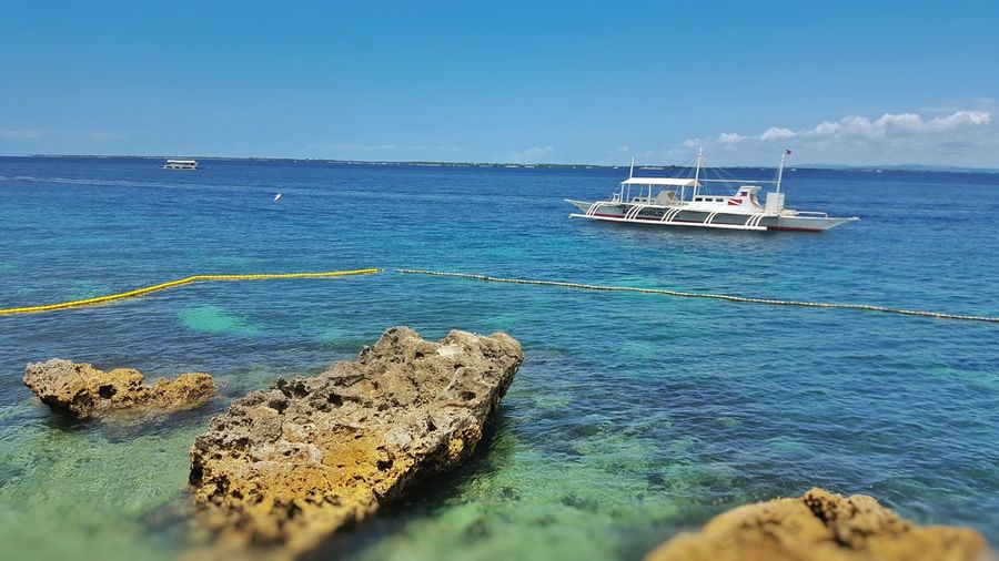 Beach Beach Photography Blue Sea And Blue Sky Blue Sea Blue Sky Rocks On The Shore Rocks And Water Rocks On The Beach Boats Boats On Beach White Boat Little Boat Beach View Resorts Resort Beach Resort Beach Resort View Cebu Philippines Mactan Mactan Cebu Mactan Island