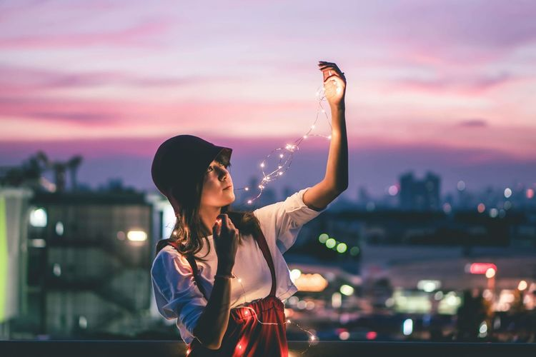 Young woman standing by illuminated city against sky during sunset