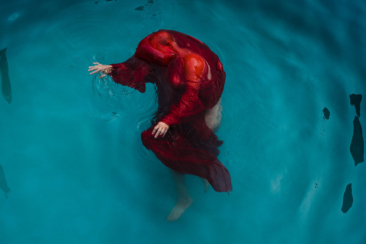 HIGH ANGLE VIEW OF WOMAN SWIMMING IN POOL AT SEA