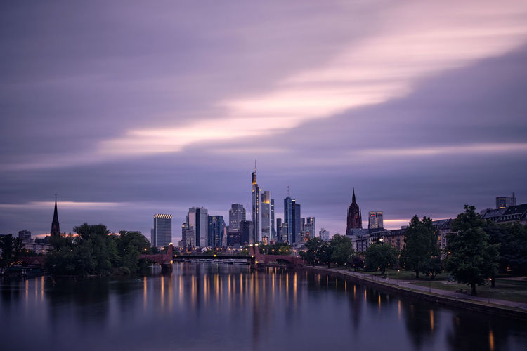 View of frankfurt am main skyline against cloudy sky during sunset