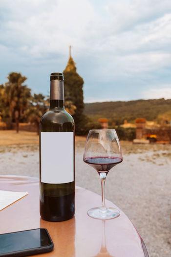 Wine glass bottle on table against sky