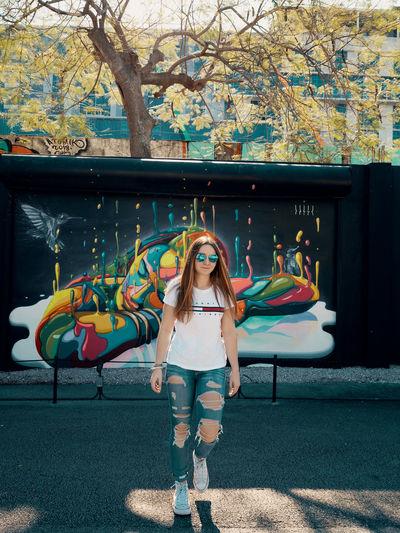 Full length portrait of woman standing against graffiti