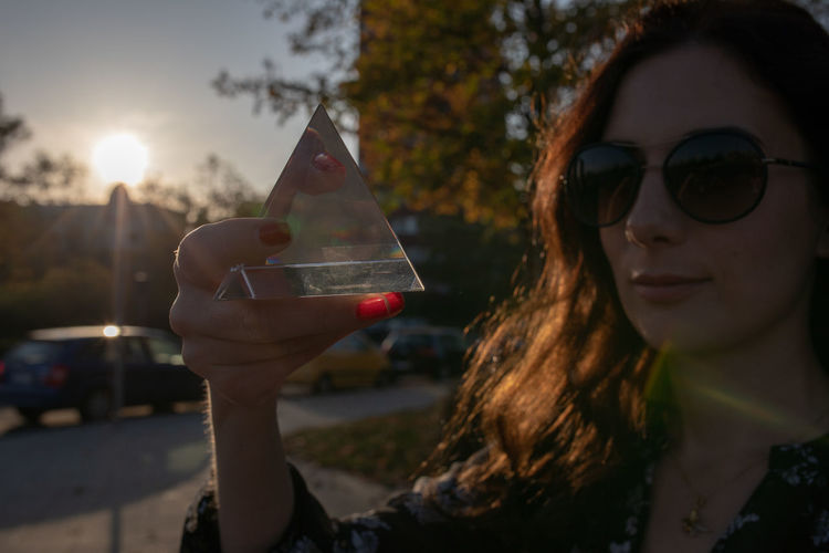 Close-up portrait of woman holding crystal in city during sunset