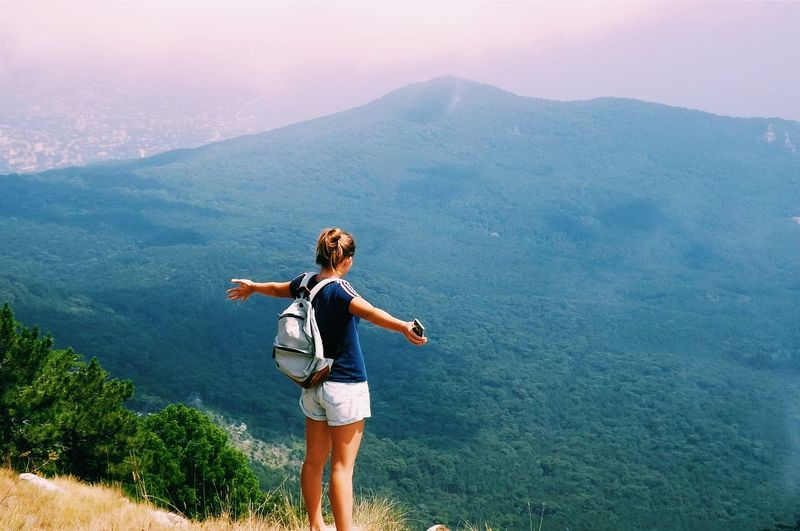 Woman with arms outstretched standing on mountain against sky