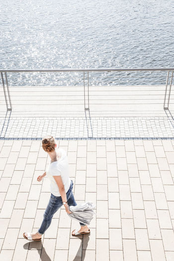 High Angle View Of Woman Walking On Promenade By Sea