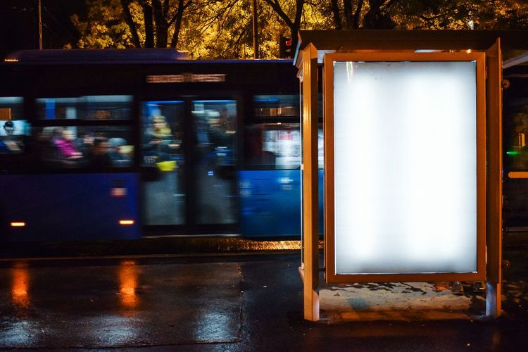 Bus by stop on street at night