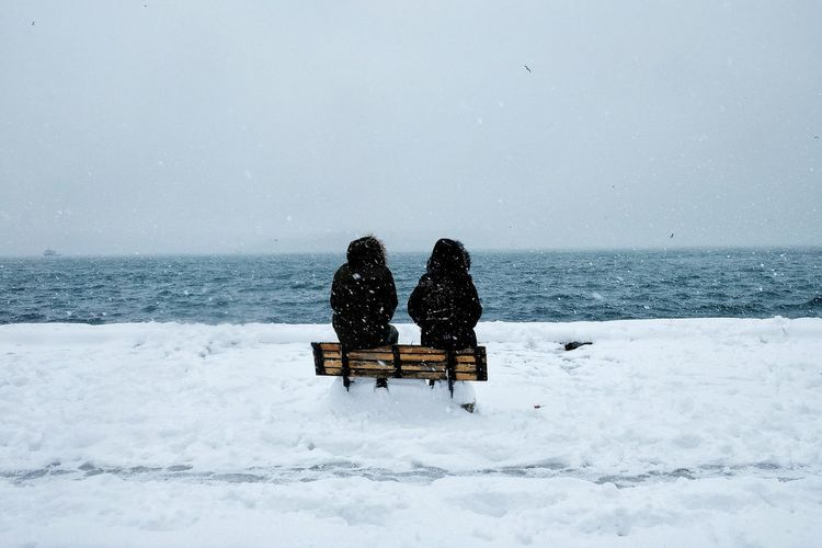 Rear View Of Friends Sitting On Bench At Beach During Snowfall