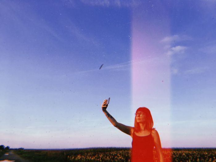Woman taking selfie against blue sky