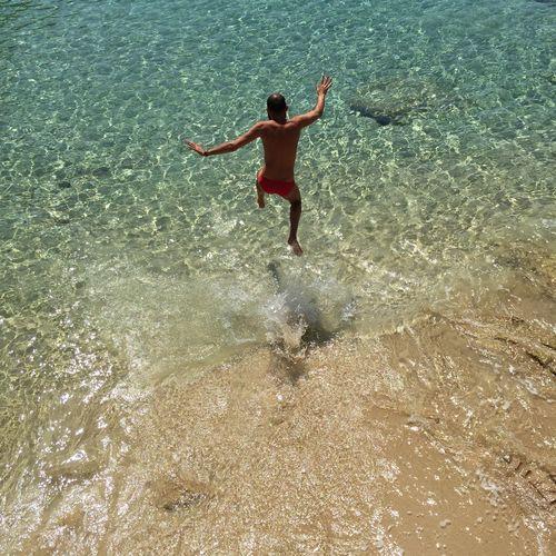 High angle view of shirtless man jumping into water at beach