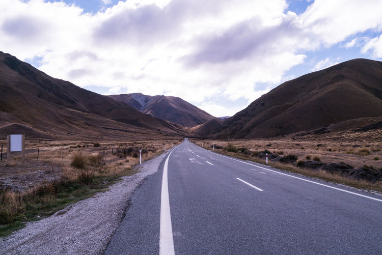 Asphalt Beauty In Nature Cloud Cloud - Sky Country Road Day Diminishing Perspective Empty Empty Road Landscape Long Mountain Mountain Range Nature Non-urban Scene Outdoors Remote Road Road Marking Scenics Sky The Way Forward Tranquil Scene Tranquility Vanishing Point